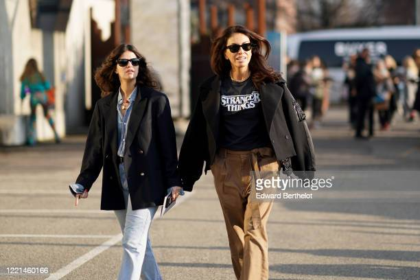 Guest wears sunglasses, a black bomber jacket, a Stranger Things t-shirt, brown pants, outside Alberta Ferretti, during Milan Fashion Week...