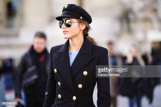 23a4f8182e2 A guest wears sunglasses a black cap a navy blue brass buttons blazer  during Paris Fashion
