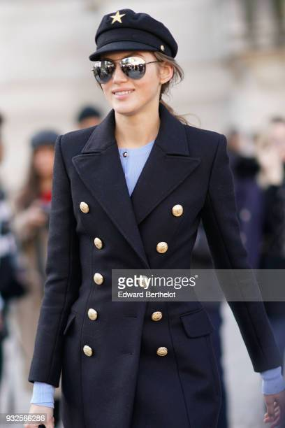 A guest wears sunglasses a black cap a navy blue doublebreasted brass buttons coat a baby blue sweater during Paris Fashion Week Womenswear...