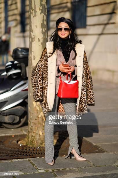 A guest wears sunglasses a black cap a taupecolour knit jacket a leopardprint coat a red handbag grey checkered fulllength ziphem pants peachcolour...