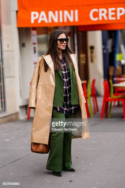 A guest wears sunglasses a black checkered tunic a green wideleg pantsuit a glossy peach colour vinyl coat a brown bag black studded pointy toe shoes...