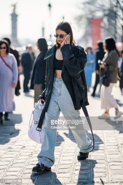 A guest wears sunglasses a black crop top a black leather oversize jacket wideleg ripped hem jeans black sneakers a shiny silver bag outside Maison...