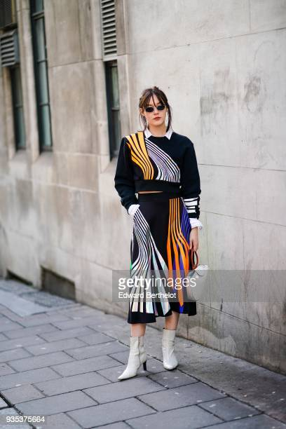 A guest wears sunglasses a black dress with colored stripes a white semicircular bag white boots during London Fashion Week February 2018 on February...