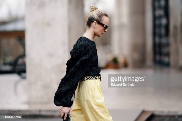 A guest wears sunglasses a black embossed fabric top with puff sleeves a yellow and black belt yellow pants outside Cedric Charlier during Paris...