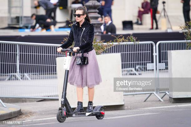 A guest wears sunglasses a black jacket a bag a purple dress black leather shoes rides a Bird electric scooter outside the Chanel Cruise Collection...
