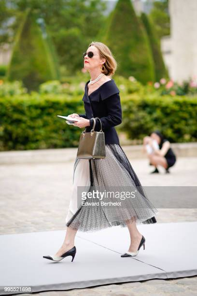 A guest wears sunglasses a black jacket a shiny bag a pleated skirt black and white shoes outside Dior during Paris Fashion Week Haute Couture Fall...