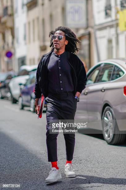 A guest wears sunglasses a black jacket a shirt cropped pants red socks white sneakers outside Wooyoungmi during Paris Fashion Week Menswear...