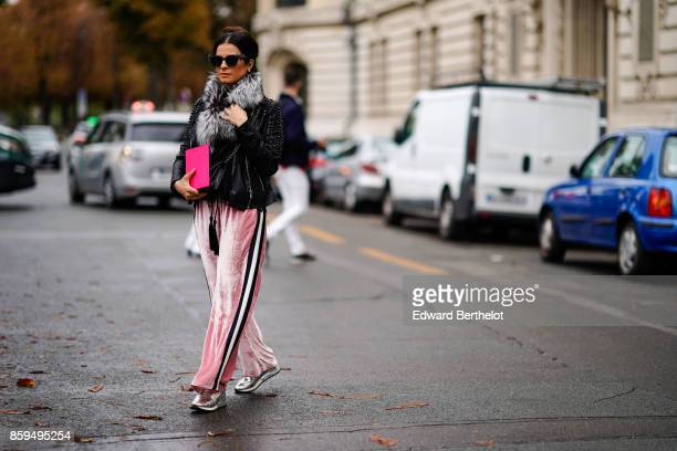 A guest wears sunglasses a black jacket with a fur collarlarge pink velvet pants with stripe and silver lame trainers outside Manish Arora during...