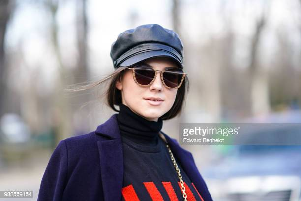 A guest wears sunglasses a black leather cap a navy blue coat a black turtleneck with red stripes during Paris Fashion Week Womenswear Fall/Winter...
