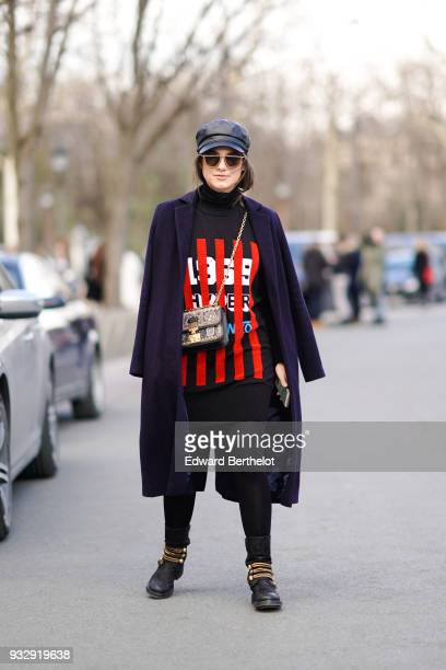 A guest wears sunglasses a black leather cap a navy blue coat a black turtleneck with red stripes and white figures on the front a black mini skirt...