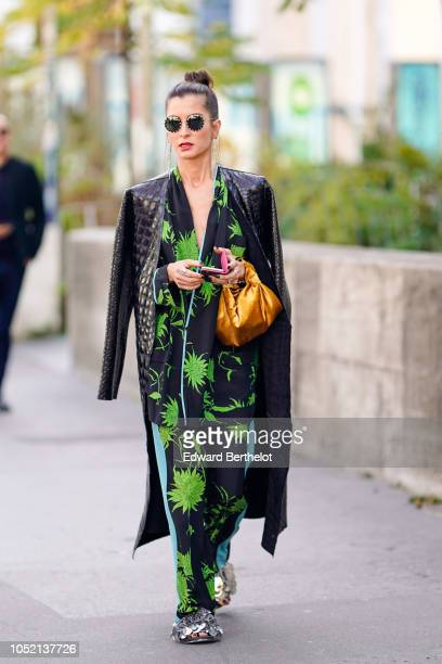 A guest wears sunglasses a black leather coat a black and green floral print kimono outfit a bag long earrings outside Haider Ackermann during Paris...