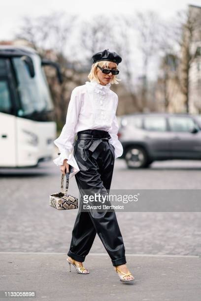 A guest wears sunglasses a black leather Dior beret hat a white victorian top black leather wideleg cuffed pants with a bow belt a beige python...