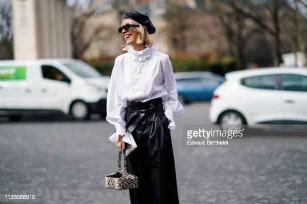 A guest wears sunglasses a black leather Dior beret hat a white victorian top black leather wideleg pants with a bow belt a beige python pattern...