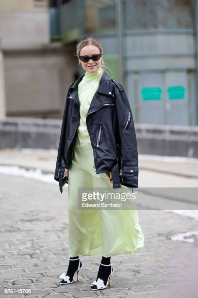 A guest wears sunglasses a black leather jacket a dress white shoes during Paris Fashion Week Womenswear Fall/Winter 2018/2019 on March 1 2018 in...