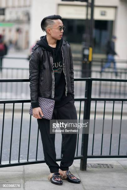 A guest wears sunglasses a black leather jacket a Gucci hoodie top a Goyard clutch shoes with fur during London Fashion Week Men's January 2018 at on...