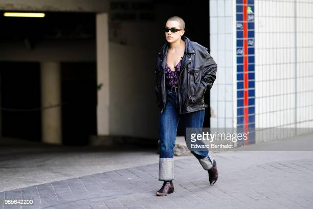 A guest wears sunglasses a black leather jacket blue denim jeans brown leather shoes outside 1017 ALYX 9SM during Paris Fashion Week Menswear...