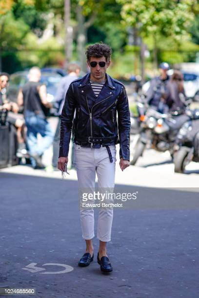 Guest wears sunglasses, a black leather jacket, white cropped pants, black leather shoes, a striped top, outside Juun J, during Paris Fashion Week -...
