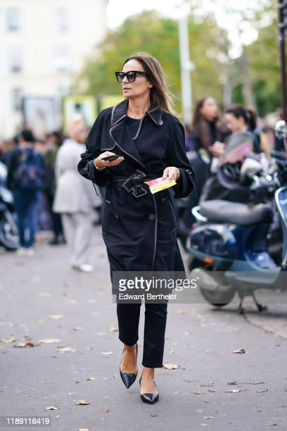 A guest wears sunglasses a black long coat pants pointy shoes outside Nina Ricci during Paris Fashion Week Womenswear Spring Summer 2020 on September...