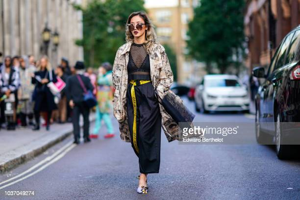A guest wears sunglasses a black mesh top black pants a yellow OffWhite belt purple shoes a beige print trench coat during London Fashion Week...