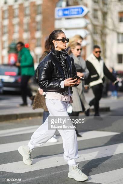 Guest wears sunglasses, a black puffer jacket, white sportswear pants, sneakers, outside Lacoste, during Paris Fashion Week - Womenswear Fall/Winter...
