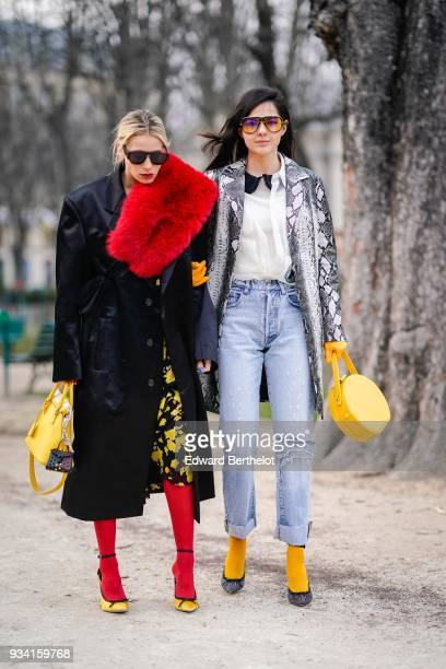 A guest wears sunglasses a black satin oversize coat a red fur stole a black dress with yellow floral print a yellow handbag red tights black trim...
