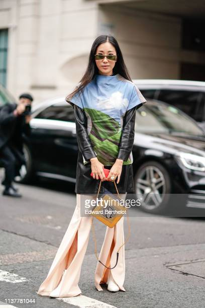 A guest wears sunglasses a black shiny tunic a blue sky and banana leaves print fitted top peachcolor front split flare pants a black and orange bag...