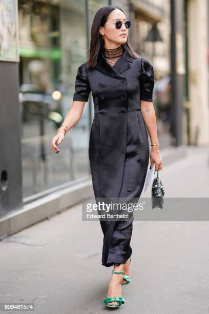 A guest wears sunglasses a black silk dress a choker green heels shoes outside the Valentino show during Paris Fashion Week Haute Couture Fall/Winter...