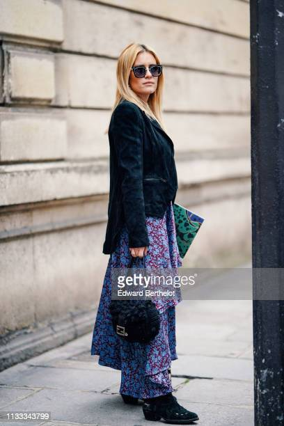 Guest wears sunglasses, a black suede jacket, a blue and red floral print ruffled dress, black suede boots, a black wool Fendi bag, outside Elie...