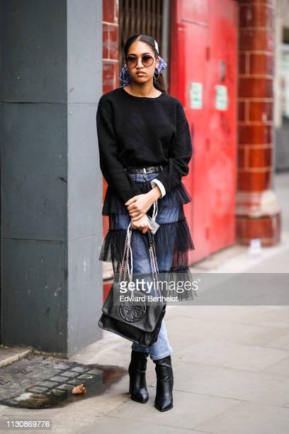 A guest wears sunglasses a black sweater a black handbag black pointy boots blue jeans under a black tulle frilly skirt during London Fashion Week...