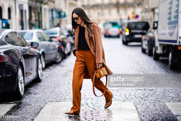 A guest wears sunglasses a black sweater a brown coat tannishyellow pants brown boots with metallic end a brown and yellow bag outside Nobi Talai...