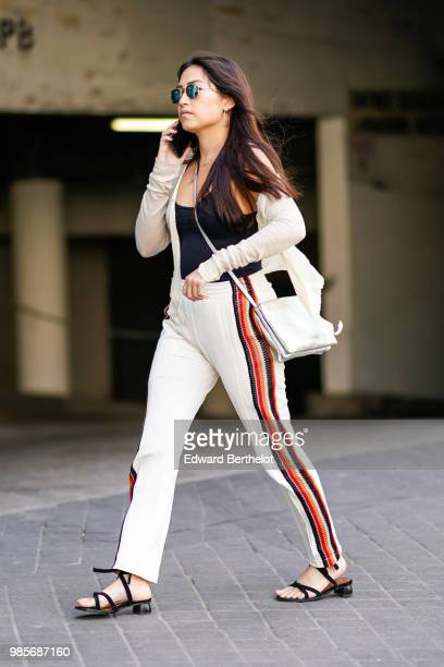 A guest wears sunglasses a black tank top a white bag white pants with colored stripes sandals outside 1017 ALYX 9SM during Paris Fashion Week...