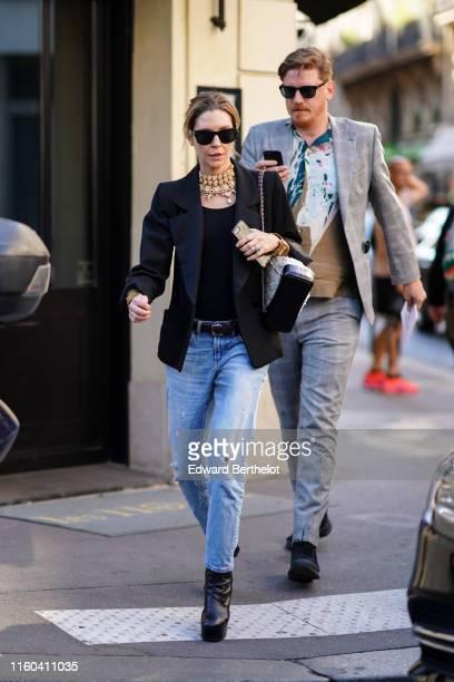 A guest wears sunglasses a black top black blazer jacket a belt blue denim jeans black shoes a large necklace outside Valentino during Paris Fashion...