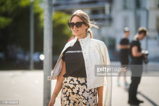 A guest wears sunglasses a black top with a white message a white Courreges hineck jacket a black skirt with white and yellow daisies print outside...