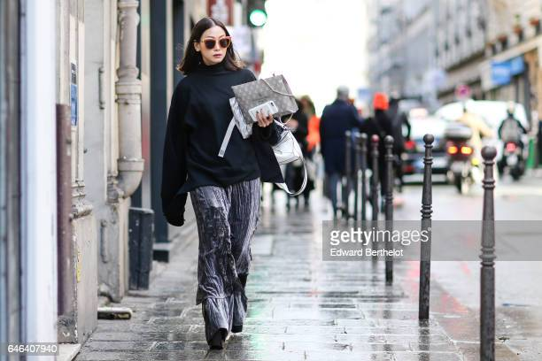 A guest wears sunglasses a black top with long sleeves gray large pants and black shoes with large heels outside the AALTO show during Paris Fashion...
