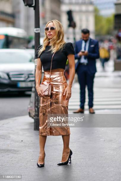 Guest wears sunglasses, a black t-shirt, a bronze color shiny skirt, a pink bag, YSL shoes, outside Ralph & Russo, during Paris Fashion Week -...