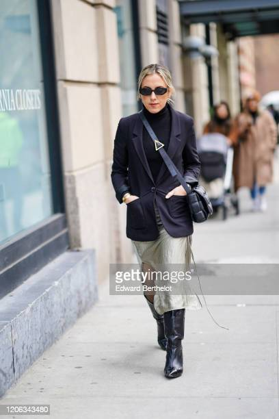 A guest wears sunglasses a black turtleneck a black jacket a flowing skirt black leather pointy boots a Bottega Veneta quilted bag during New York...