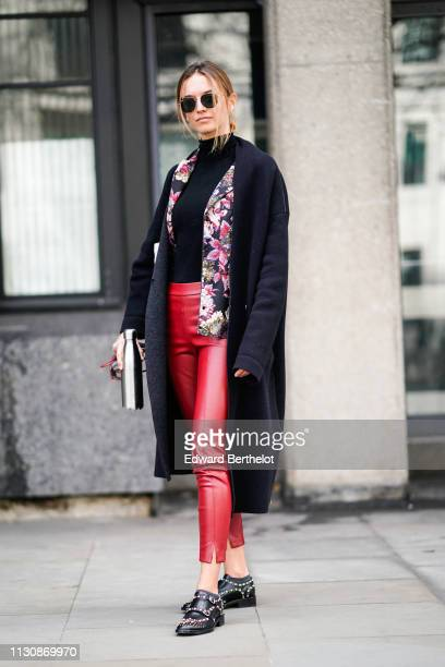 A guest wears sunglasses a black turtleneck a floral print jacket a black coat red leather pants black studded shoes during London Fashion Week...