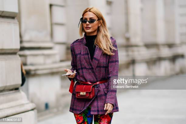 A guest wears sunglasses a black turtleneck a purple tartan jacket a red studded beltbag colorful skinny pants with printed images of Marylin Monroe...