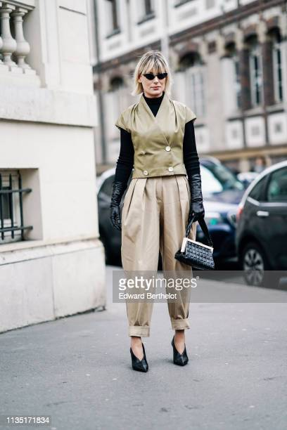 A guest wears sunglasses a black turtleneck long black gloves a light khaki sleeveless doublebreasted jacket pleated beige cuffed pants black pointy...