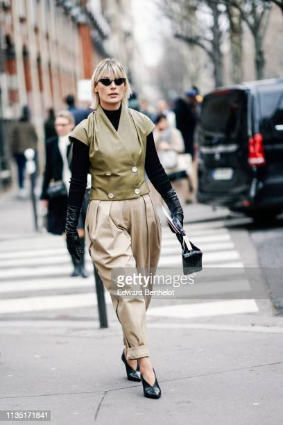 Guest wears sunglasses, a black turtleneck, long black gloves, a light khaki sleeveless double-breasted jacket, pleated beige cuffed pants, black...