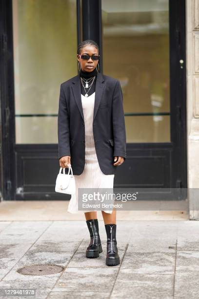 Guest wears sunglasses, a black turtleneck pullover, a black oversized blazer jacket, a white dress, black leather boots, a white bag, necklace,...