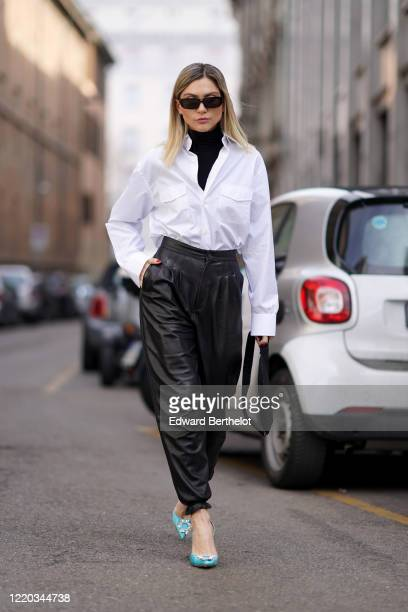 Guest wears sunglasses, a black turtleneck pullover, a white shirt, black leather pants, blue shoes, a Prada bag, outside Sportmax, during Milan...