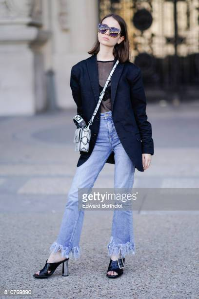 A guest wears sunglasses a blazer jacket a black mesh top blue denim flared ripped jeans pants black shoes outside the Ralph Russo show during Paris...