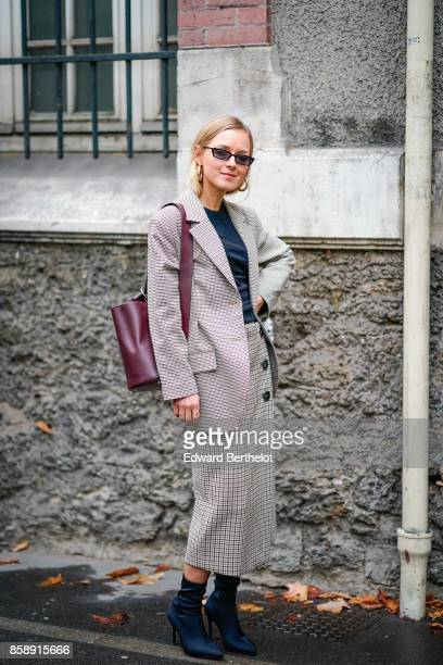 A guest wears sunglasses a blazer jacket a red bag a skirt blue shoes outside Valentino during Paris Fashion Week Womenswear Spring/Summer 2018 on...