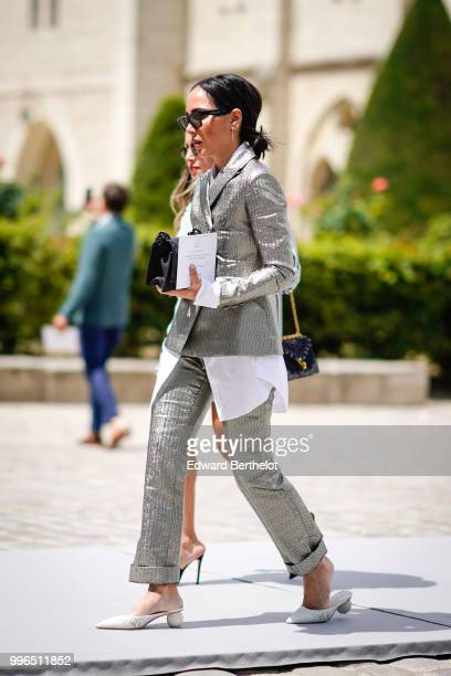 A guest wears sunglasses a blazer jacket suit pants white shoes outside Dior during Paris Fashion Week Haute Couture Fall Winter 2018/2019 on July 2...