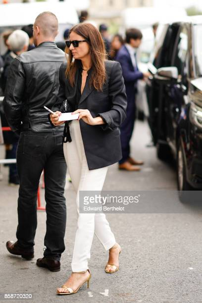 A guest wears sunglasses a blazer jacket white pants heels outside Giambattista Valli during Paris Fashion Week Womenswear Spring/Summer 2018 on...
