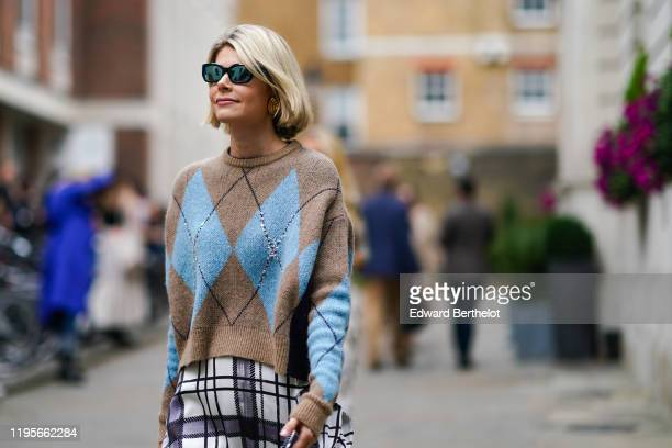 Guest wears sunglasses, a blue and brown wool pullover with printed geometric patterns, a black and white checked skirt, during London Fashion Week...
