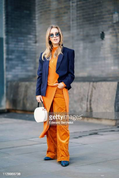 A guest wears sunglasses a blue blazer jacket orange flare corduroy trousers an orange wool pullover a white round bag during London Fashion Week...