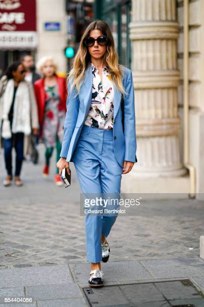 A guest wears sunglasses a blue blazer jacket suit pants a bird print shirt outside Anrealage during Paris Fashion Week Womenswear Spring/Summer 2018...