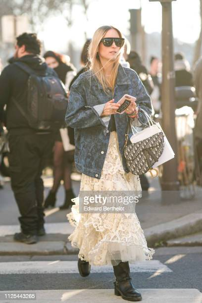A guest wears sunglasses a blue denim jacket a lace dress a Dior Saddle bag outside Dior during Paris Fashion Week Haute Couture Spring Summer 2020...